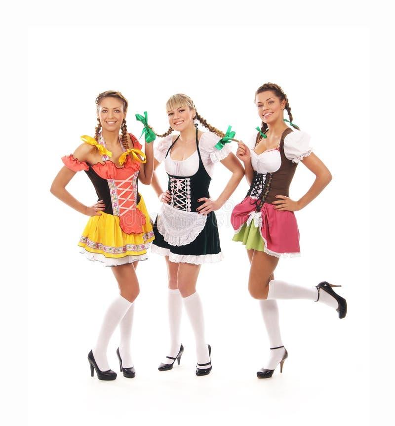 Drie jonge en gelukkige vrouwen in Beierse kleren stock foto