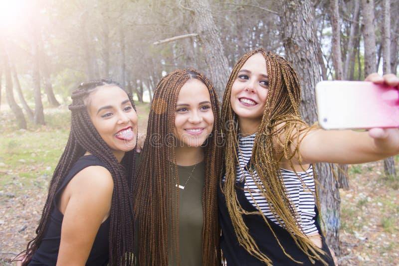 Drie jonge en mooie meisjes, met gevlecht haar, die selfie nemen stock foto's