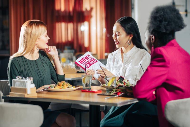 Drie jonge enige vrouwen die boek over het vinden van echtgenoot lezen stock foto's