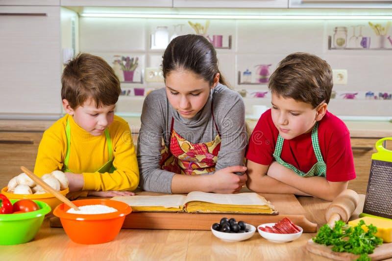 Drie jonge geitjes die het kokboek lezen stock foto