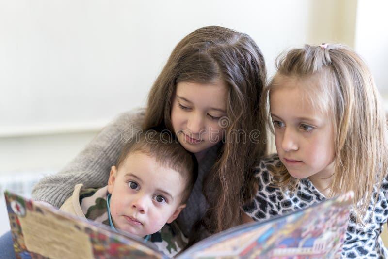 Drie jonge geitjes die pret hebben die een boek lezen Twee zusters en een broer Lichte achtergrond Europese verschijning royalty-vrije stock fotografie
