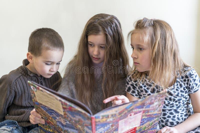 Drie jonge geitjes die pret hebben die een boek lezen Twee zusters en een broer Lichte achtergrond Europese verschijning royalty-vrije stock foto's