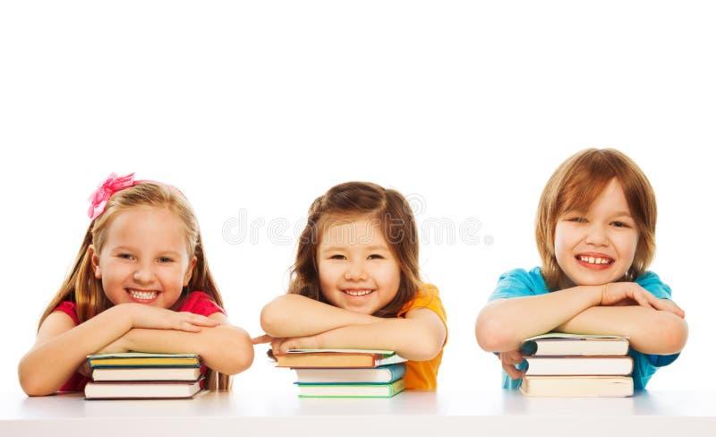 Drie slimme jonge geitjes op stapel van boeken royalty-vrije stock foto