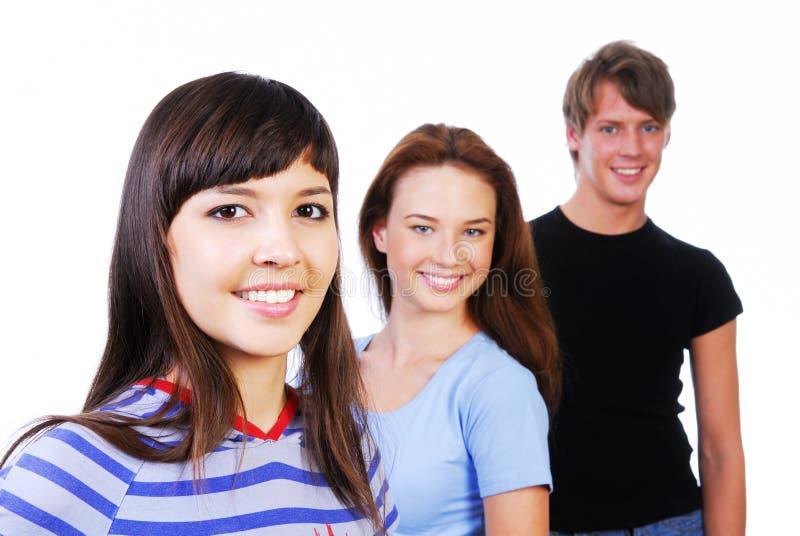 Drie jonge het glimlachen tienerjaren stock fotografie