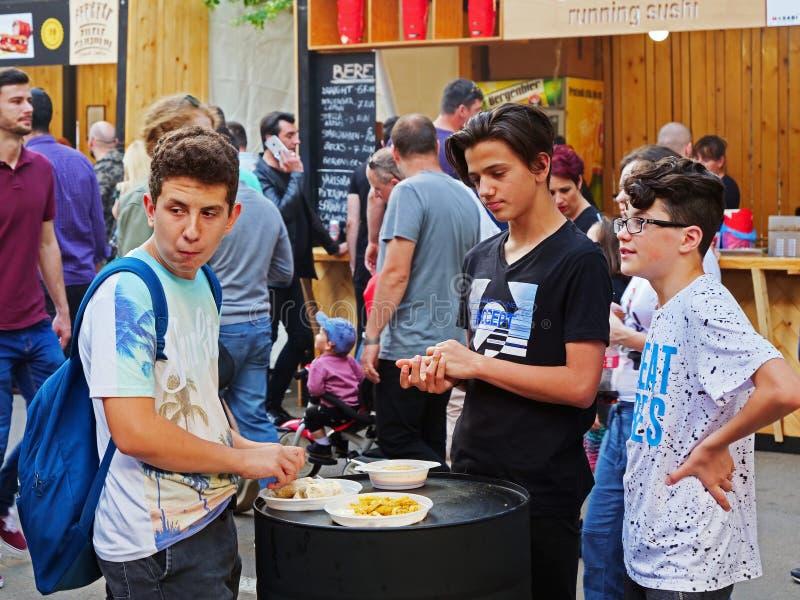 Drie jonge jongens eten snel voedsel stock foto's