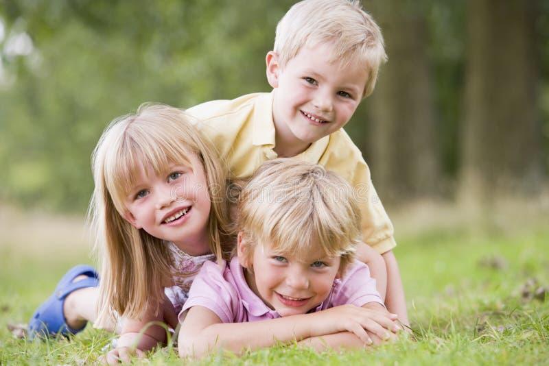 Drie jonge kinderen die in openlucht het glimlachen spelen stock foto's