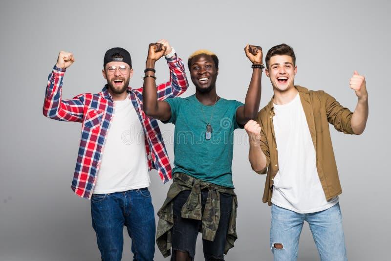 Drie jonge knappe die fans mengden rasmensen met overwinningsteken op witte backgroynd wordt geïsoleerd stock fotografie
