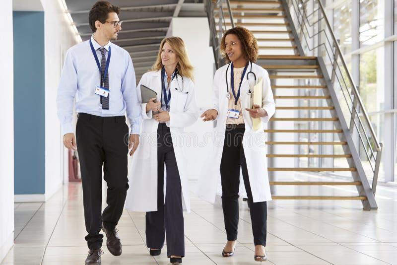 Drie jonge mannelijke en vrouwelijke artsen die in het ziekenhuis lopen royalty-vrije stock afbeeldingen