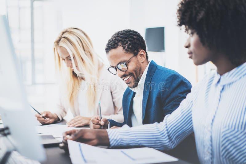 Drie jonge medewerkers die in een modern bureau samenwerken Mens die glazen dragen en nota's met collega op documenten maken hori stock afbeeldingen