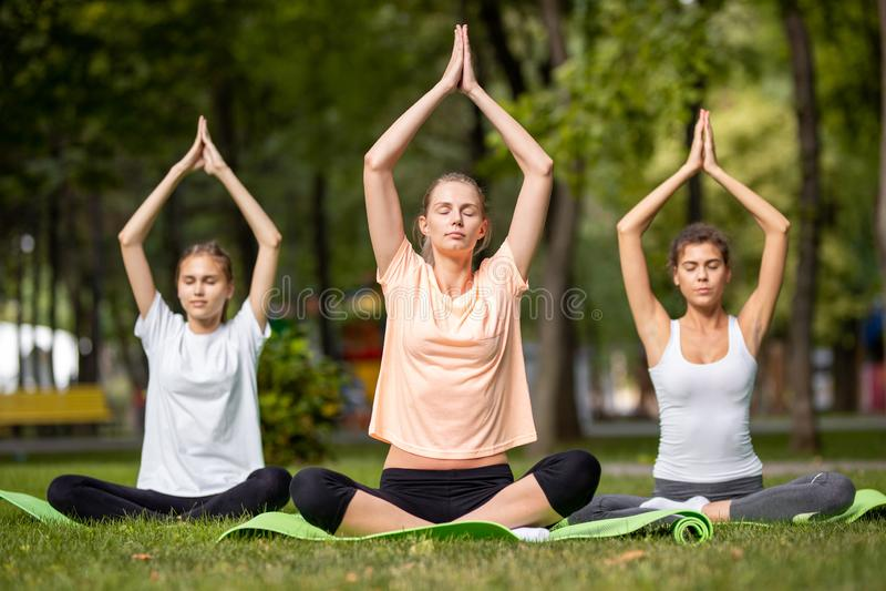 Drie jonge meisjes die yogazitting op yogamatten doen op groen gras in het park op een warme dag royalty-vrije stock foto's