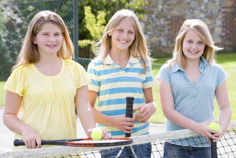 Drie jonge meisjesvrienden bij tennisbaan het glimlachen royalty-vrije stock afbeelding