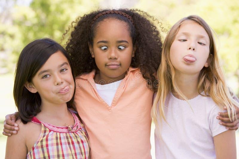 Drie jonge meisjesvrienden die grappige gezichten maken stock afbeeldingen