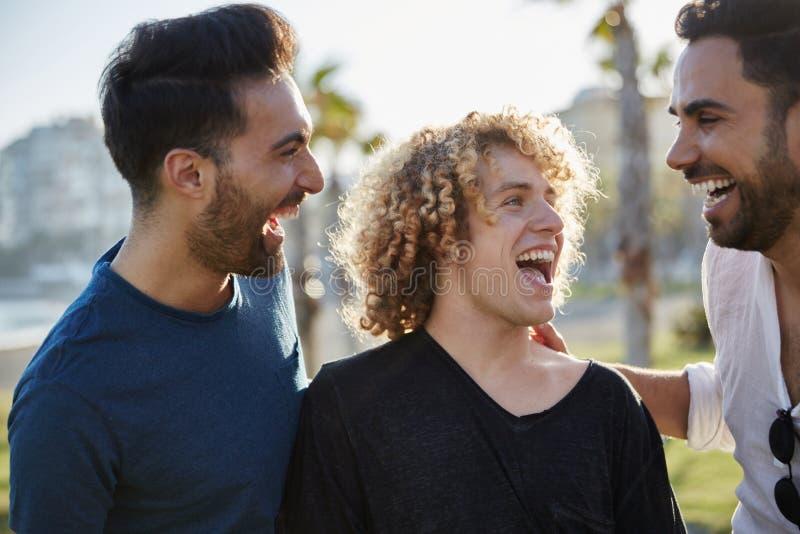 Drie jonge mensen die samen buitenkant het lachen spreken royalty-vrije stock foto's