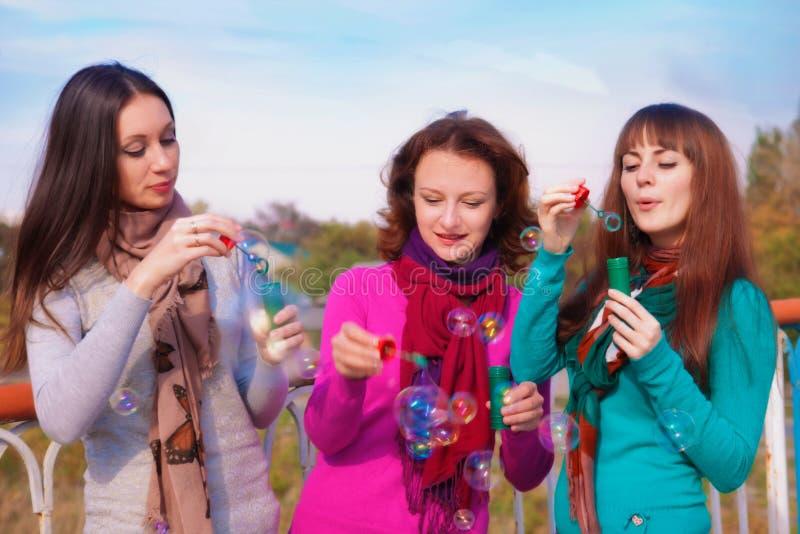 Drie jonge mooie vrouwen blazen bellen stock foto's