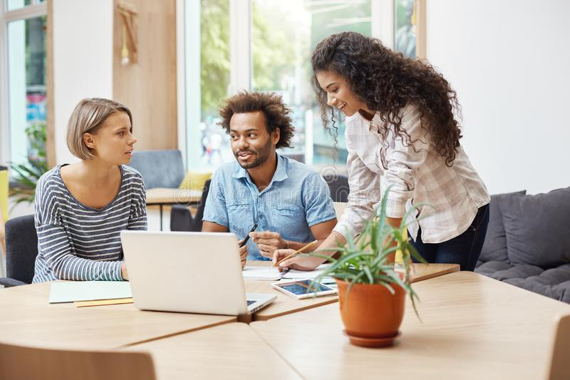 Drie jonge potentiële ondernemers die bij bibliotheek zitten, besprekend businessplannen en bedrijf` s winsten, het maken royalty-vrije stock afbeelding