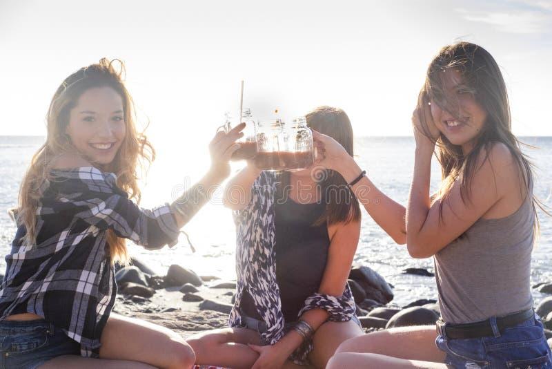 Drie jonge schoonheidsvrouwen bij het strand die een vruchtensap drinken stock afbeelding