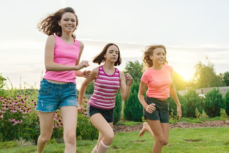 Drie jonge tieners die van sportenmeisjes op een groen gazon tegen de achtergrond van de zomerzonsondergang lopen royalty-vrije stock foto's