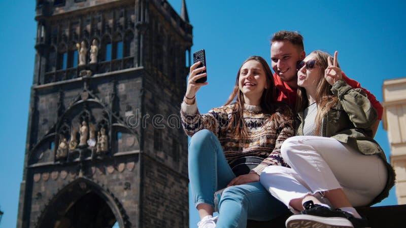 Drie jonge vrienden die en nemen een selfie onder de oude toren glimlachen Tsjech, Praag royalty-vrije stock afbeeldingen