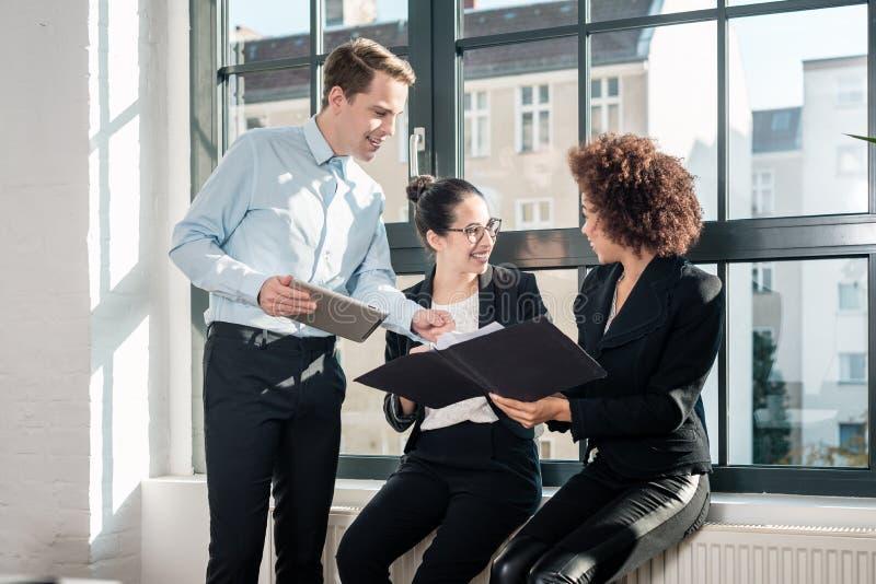 Drie jonge vrolijke werknemers die in een modern bureau glimlachen royalty-vrije stock afbeeldingen