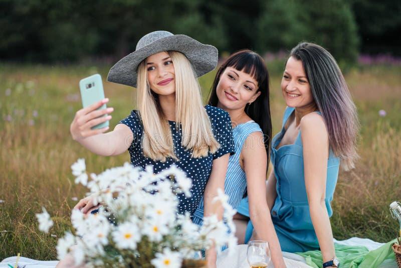 Drie jonge vrouwen, in blauwe kleding en hoeden zitten op een plaid en nemen beelden op een smartphone Openluchtpicknick op stock fotografie