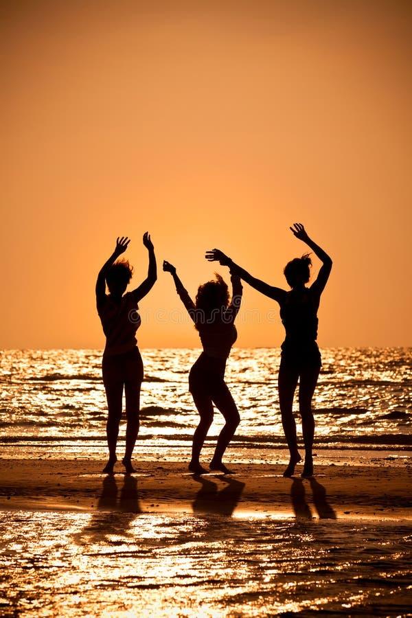 Drie Jonge Vrouwen die op Strand bij Zonsondergang dansen stock foto's