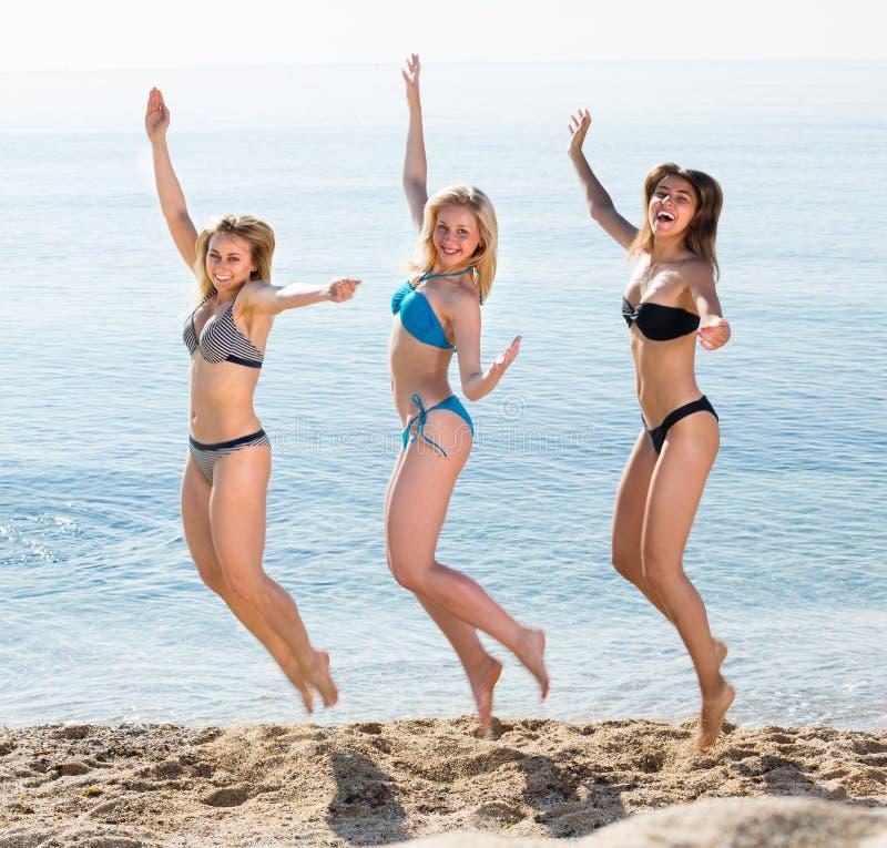 Drie jonge vrouwen die op zandig strand springen stock foto