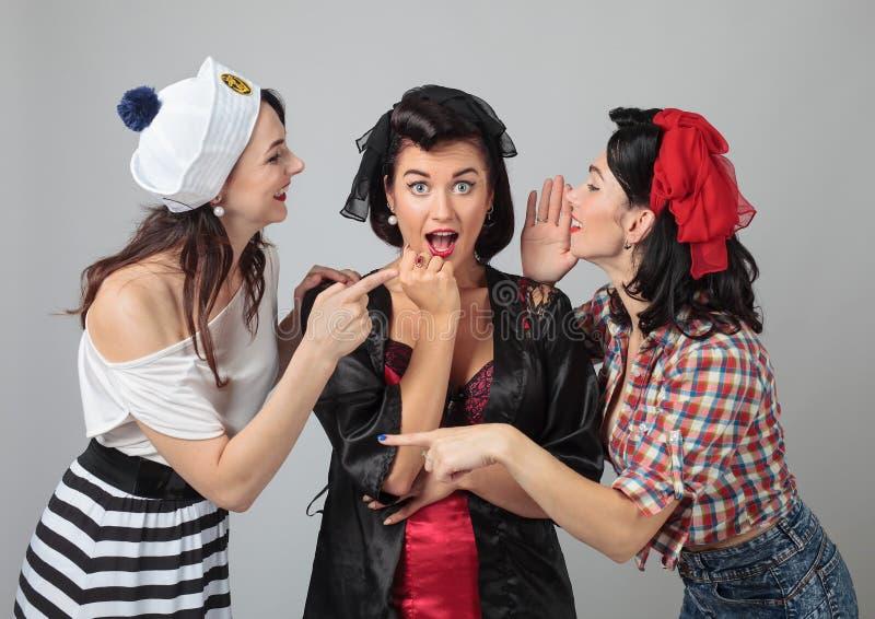 Drie jonge vrouwen die roddel fluisteren stock afbeeldingen