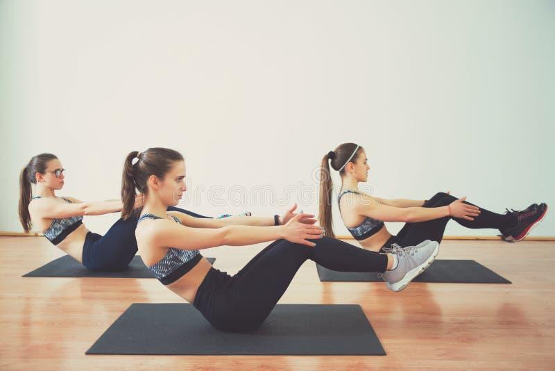 Drie jonge vrouwen die training samen in gymnastiek doen Geschiktheid en levensstijlconcept royalty-vrije stock fotografie