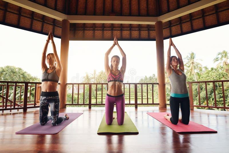 Drie jonge vrouwen die yoga doen bij gezondheidsclub stock afbeelding