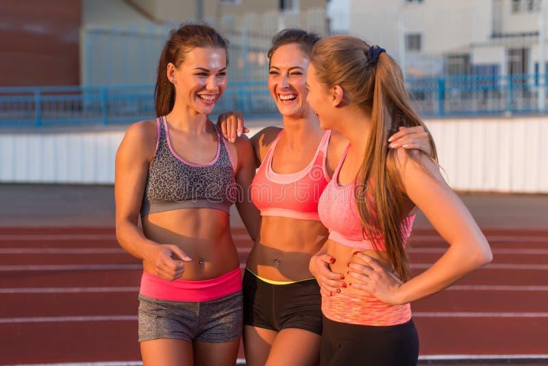 Drie jonge vrouwen die zich en in stadion glimlachen verenigen stock fotografie