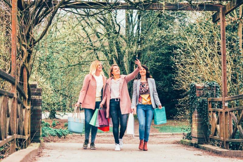 Drie jonge vrouwen in een park die een selfie met een smartphone nemen royalty-vrije stock foto's
