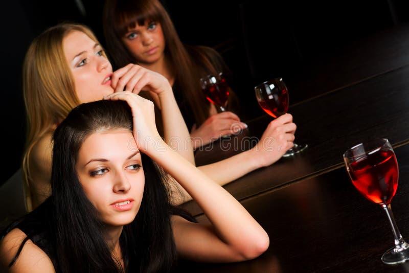 Drie jonge vrouwen in een staaf. stock foto's