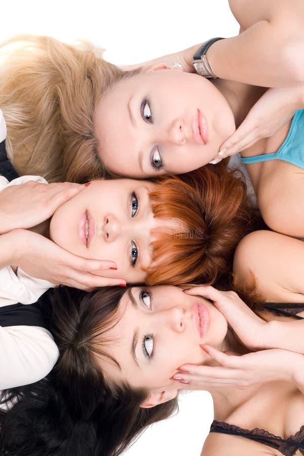 Drie jonge vrouwen wat betreft hun wangen stock fotografie