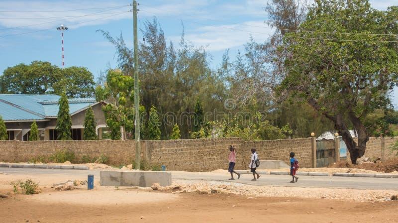 Drie jongens die aan school in Kenia Afrika lopen stock afbeeldingen