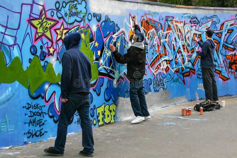 Drie jongens die graffiti schilderen stock foto