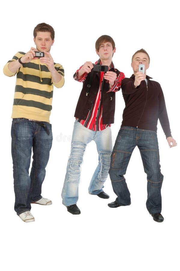 Drie Jongens Die Iets Op Mobiele Telefoon Ontspruiten Stock Afbeelding
