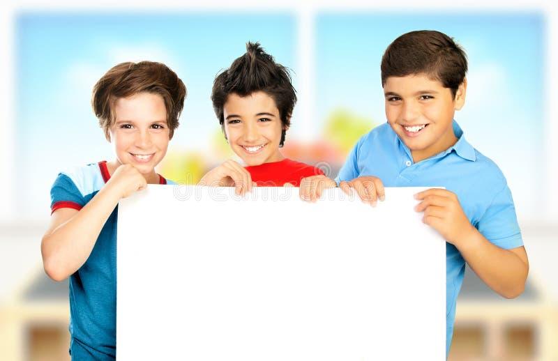 Drie jongens die in klaslokaal witte schone raad houden stock foto