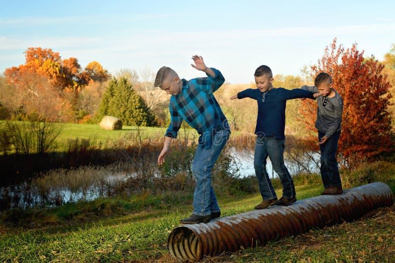 Drie jongens die op een duiker in evenwicht brengen stock afbeeldingen