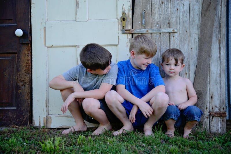 Drie jongens die tegen oude doorstane deuren zitten stock afbeeldingen