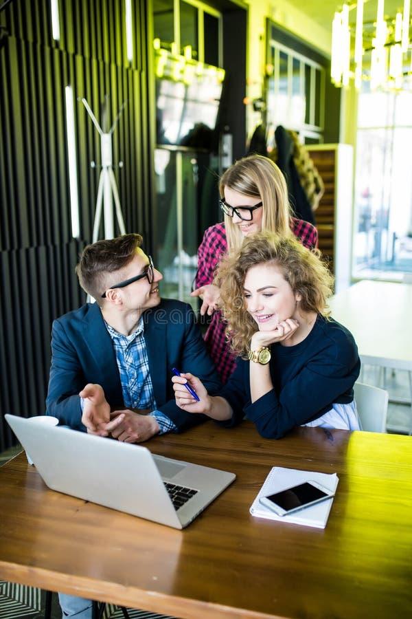 Drie jongeren die aan een nieuw project samenwerken Team van gelukkige bureaumensen die aan laptop computer, het glimlachen werke stock fotografie