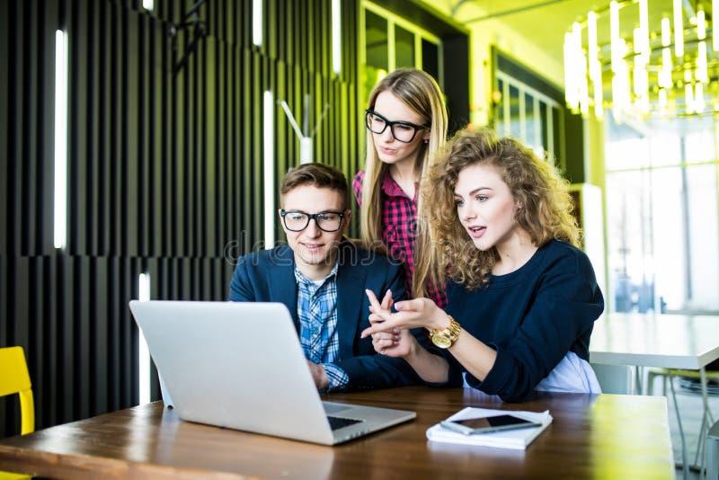Drie jongeren die aan een nieuw project samenwerken Team van gelukkige bureaumensen die aan laptop computer, het glimlachen werke stock afbeelding