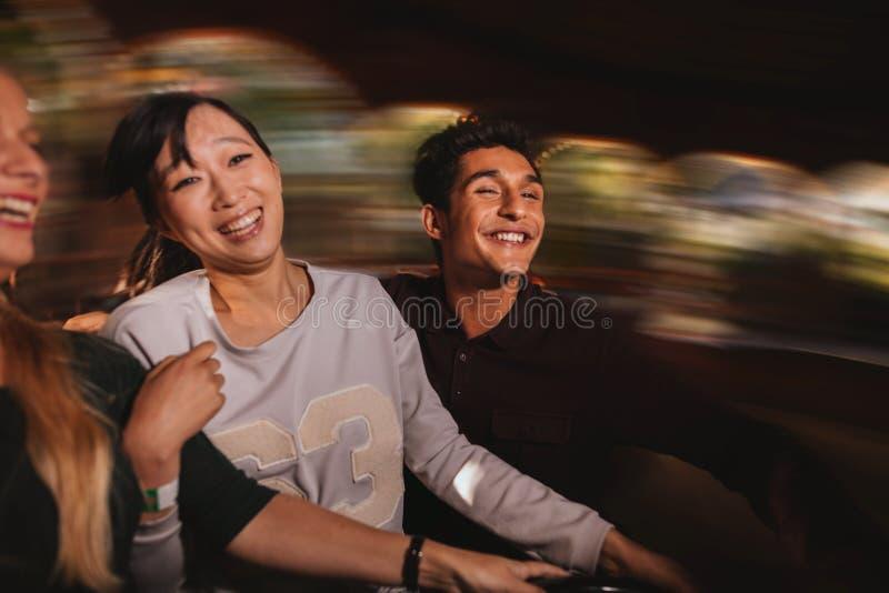 Drie jongeren op pretpark berijdt royalty-vrije stock foto's
