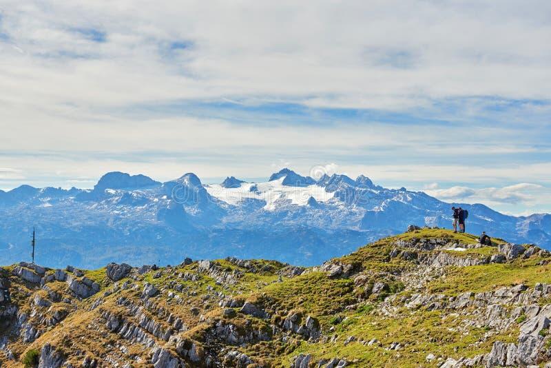 Drie jongeren zit op Berg en bekijkt in Smartphone Salzkammergut, gebied, Alpen, Oostenrijk royalty-vrije stock foto
