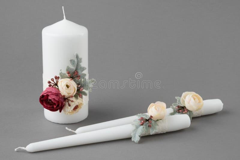 Drie kaarsen die met bloemen op grijze achtergrond worden verfraaid stock foto's