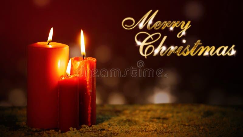 Drie kaarsen op grond met Vrolijke Kerstmisteksten stock afbeeldingen