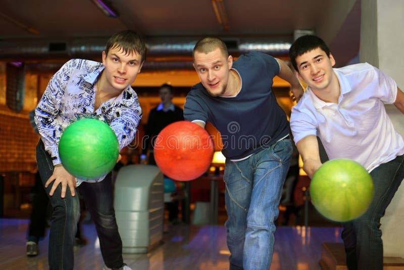 Drie kameraden werpen ballen op steeg in kegelenclub royalty-vrije stock afbeelding