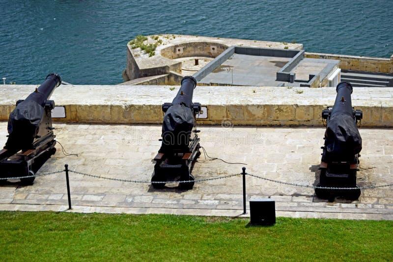 Drie kanonnen op een rij allen die uit aan de Middellandse Zee in Valletta Malta onder ogen zien royalty-vrije stock fotografie