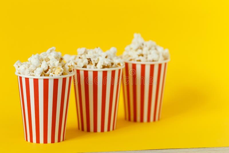 Drie kartonemmer met bioskoopsnack popcorn en rode koppen op kleuren gele achtergrond Ruimte voor tekst stock foto's