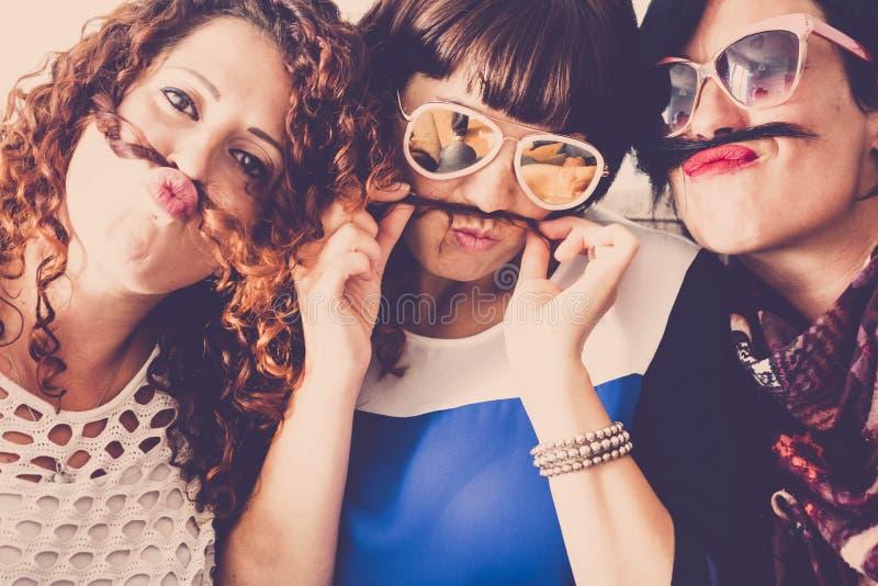 Drie Kaukasische wijfjesvrienden blijven samen in vriendschap en gekheid gebruikend haar zoals snor en gelukverhouding royalty-vrije stock fotografie