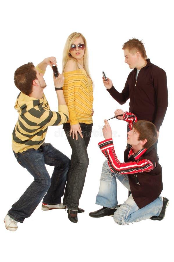 Drie kerels maken foto van een meisje door mobiel stock fotografie